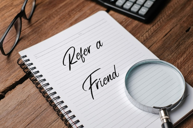 Vue de dessus de la loupe, du crayon et du cahier écrit avec refer a friend sur fond en bois.