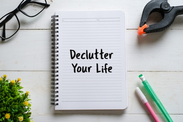 Vue de dessus des lunettes, crayon, plante, stylo avec écrit à la main ' declutter your life ' sur ordinateur portable sur fond de bois blanc.
