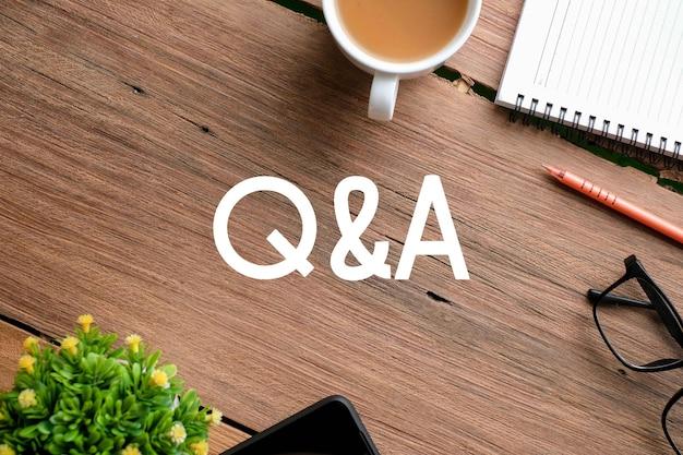 Vue de dessus des lunettes et planche de bois écrite avec le texte q et a sur fond de bois. un concept d'entreprise.