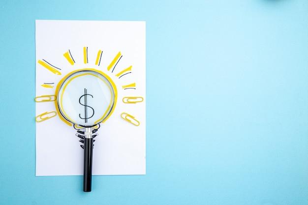 Vue de dessus lupa sur papier business idée ampoule photo sur fond bleu copie lieu