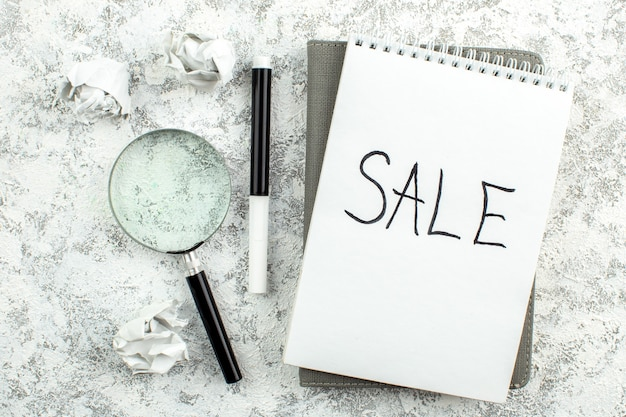 Vue de dessus lupa et vente de marqueurs écrits sur papier sur table