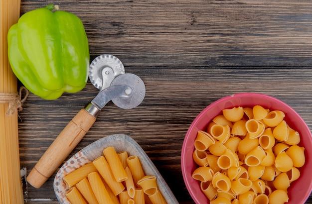 Vue de dessus des macaronis comme ziti et pipe-rigate dans des bols avec du poivre sur bois