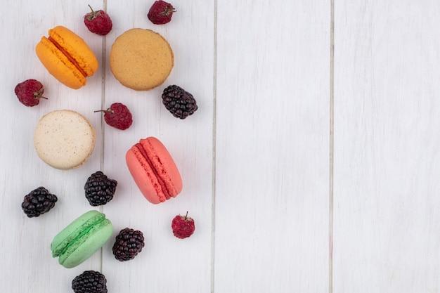 Vue de dessus des macarons colorés aux framboises et mûres sur une surface blanche
