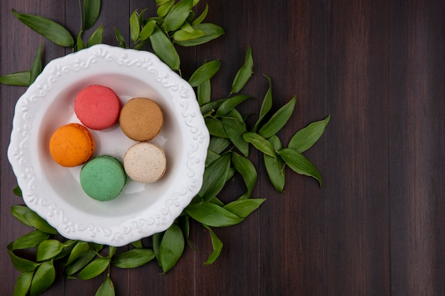 Vue de dessus des macarons colorés dans une assiette avec des branches de feuilles sur une surface en bois