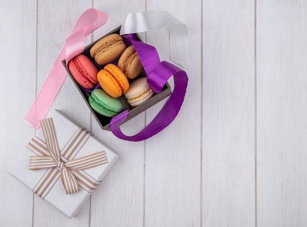 Vue de dessus des macarons colorés dans une boîte avec des arcs colorés et du papier cadeau sur une surface blanche