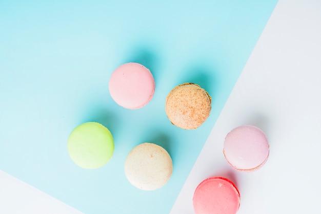 Une vue de dessus de macarons colorés sur double fond bleu et blanc
