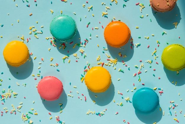 Vue de dessus des macarons colorés épars et des pépites de sucre sur fond bleu. abstrait alimentaire.