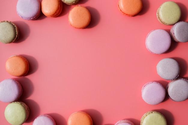 Une vue de dessus de macarons avec un espace de copie pour écrire le texte sur le fond corail
