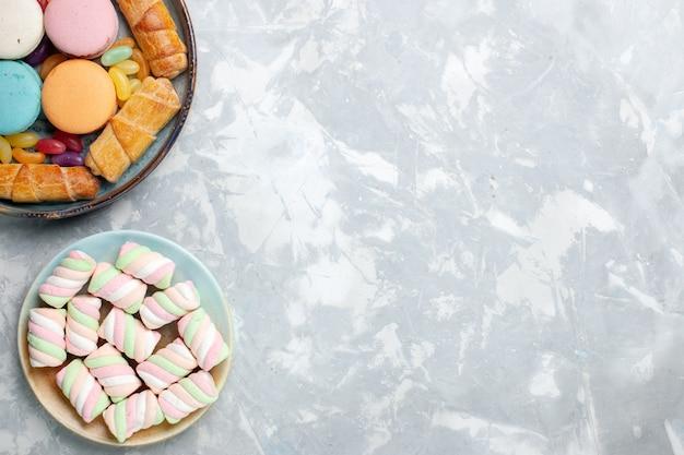 Vue de dessus macarons français avec bagels et guimauves sur blanc