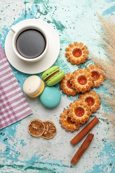 Vue de dessus macarons français avec des biscuits et une tasse de thé sur une surface bleue