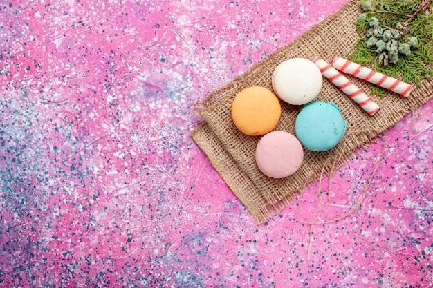 Vue de dessus macarons français colorés avec des bonbons sur le bureau rose clair cuire le gâteau couleur de tarte au sucre sucré