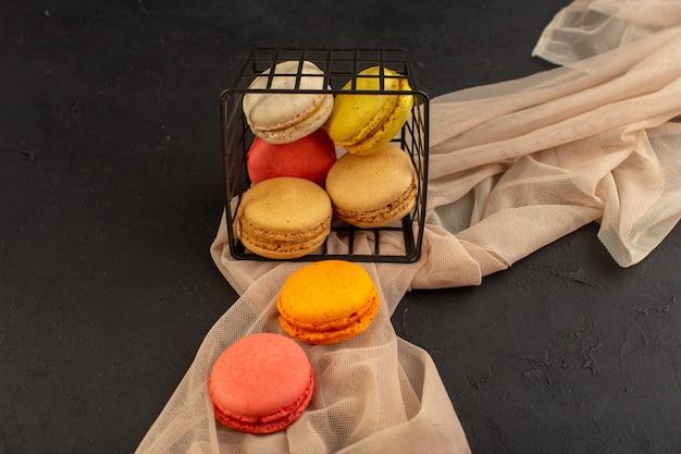 Une vue de dessus macarons français colorés délicieux et cuit au four à l'intérieur du panier sur la table noire biscuit gâteau biscuit sucre