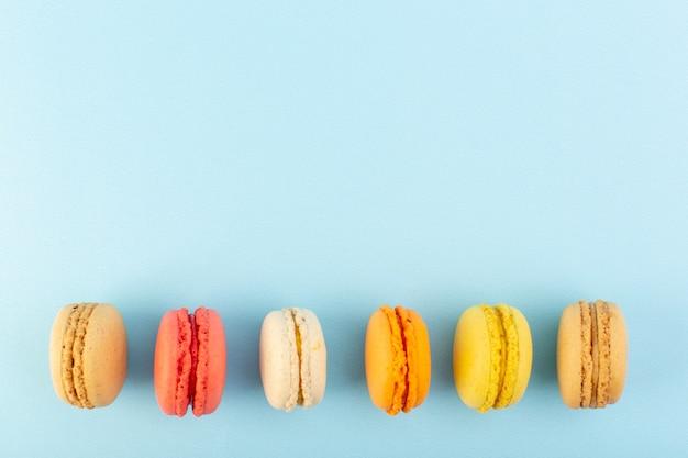Une vue de dessus macarons français colorés délicieux et cuits au four sur la table bleue