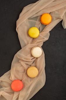 Une vue de dessus macarons français colorés délicieux et cuits au four sur la table noire biscuit gâteau biscuit sucre