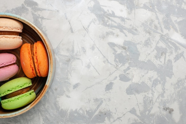 Vue de dessus macarons français colorés délicieux petits gâteaux sur un bureau blanc