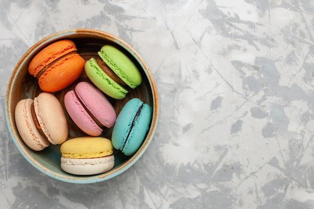 Vue de dessus macarons français colorés délicieux petits gâteaux sur une surface blanche