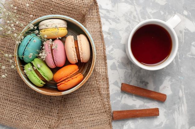 Vue de dessus macarons français colorés délicieux petits gâteaux avec tasse de thé sur un bureau blanc
