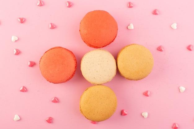 Une vue de dessus des macarons français colorés formés de délicieux sur le gâteau de bureau rose biscuit sucre sucré