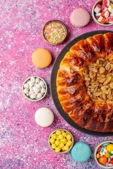 Vue de dessus macarons français colorés petits gâteaux délicieux avec des bonbons et tarte aux raisins secs sur le bureau rose biscuit biscuit gâteau tarte au sucre