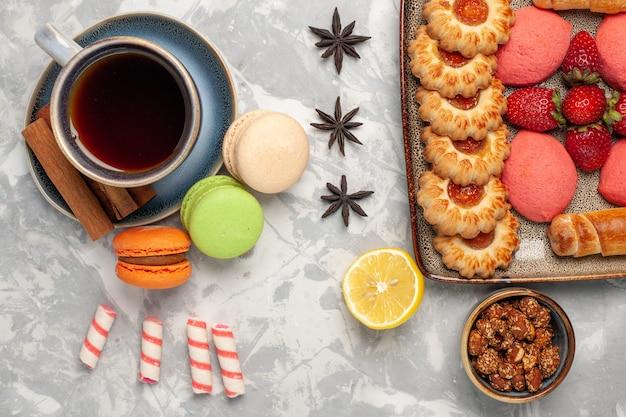 Vue de dessus macarons français avec des fraises rouges fraîches et des cookies sur une surface blanche
