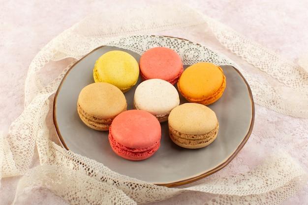Une vue de dessus macarons français rond et délicieux à l'intérieur de la plaque sur la table rose gâteau biscuit sucre sucré