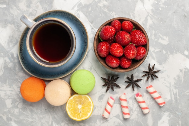 Vue de dessus macarons français avec tasse de thé et fraises sur une surface blanche