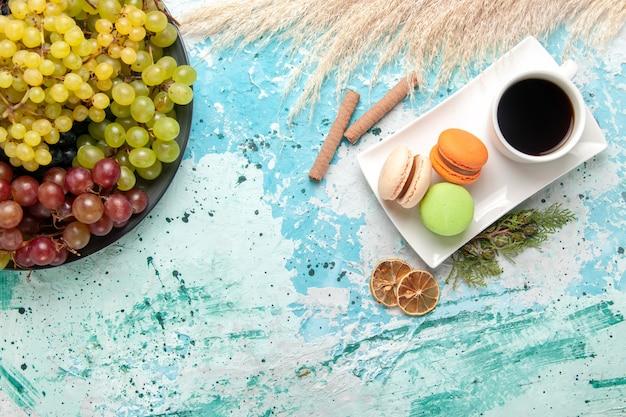 Vue de dessus macarons français avec tasse de thé et raisins frais sur fond bleu gâteau biscuit tarte au sucre sucré