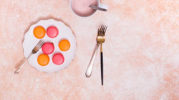 Une vue de dessus de macarons sur une plaque en céramique blanche avec des fourches sur le fond texturé