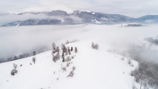 Vue de dessus d'un magnifique paysage fascinant de montagnes enneigées et de collines avec des arbres et du brouillard par une journée froide d'hiver nuageux