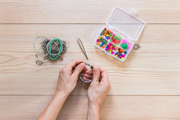 Une vue de dessus de main faisant des bijoux faits à la main sur le bureau