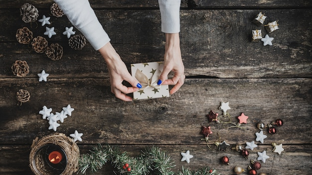 Vue de dessus d'une main féminine attachant un arc doré au-dessus d'une boîte-cadeau de vacances sur un bureau en bois rustique avec des ornements de noël, une décoration et une bougie placée partout.