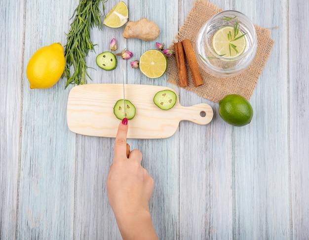 Vue de dessus de la main féminine coupant des tranches de concombre sur une planche de cuisine en bois avec des bâtons de cannelle avec un verre d'eau sur un sac en tissu sur bois gris