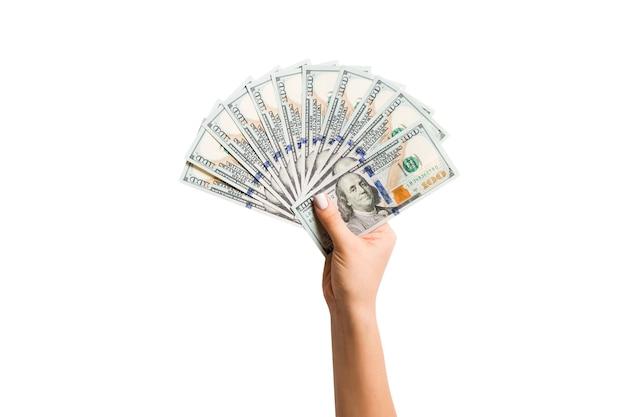 Vue de dessus d'une main féminine isolée tenant un ventilateur de billets de cent dollars. richesse et riche concept.