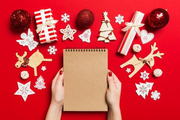 Vue de dessus de la main féminine en prenant des notes dans noteebok sur fond colful. décations et jouets du nouvel an. concept de temps de noël