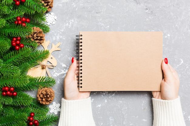 Vue de dessus d'une main féminine tenant un cahier sur fond de noël de ciment. sapin et décations de fête. liste de souhaits. concept du nouvel an