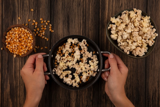 Vue de dessus de la main féminine tenant une casserole avec des pop-corn avec des grains de maïs sur un bol en bois sur une table en bois