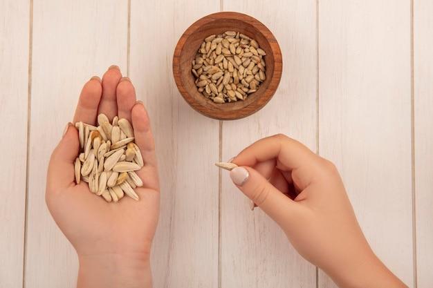 Vue de dessus de la main féminine tenant des graines de tournesol blanc avec des graines de tournesol décortiquées sur un bol en bois sur une table en bois beige