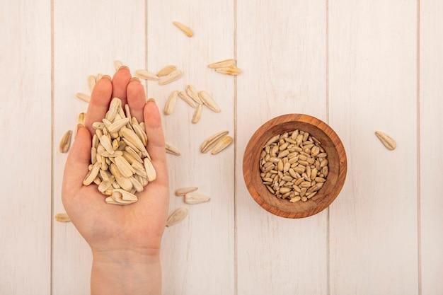 Vue de dessus de la main féminine tenant de savoureuses graines de tournesol blanc salé avec des graines de tournesol décortiquées sur un bol en bois sur une table en bois beige