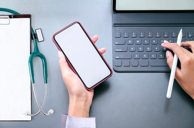 Vue de dessus main féminine tenant le smartphone avec écran blanc et travaillant avec tablette.