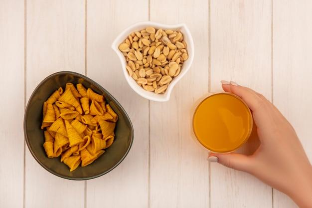 Vue de dessus de la main féminine tenant un verre de jus d'orange avec un bol de collations de maïs en forme de cône avec des pignons de pin sur un bol blanc sur une table en bois beige