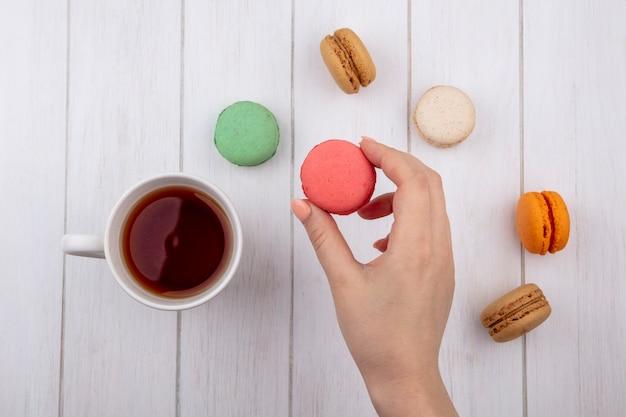 Vue de dessus de la main féminine tient des macarons multicolores avec une tasse de thé sur une surface blanche