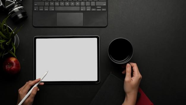 Vue de dessus de la main féminine travaillant avec tablette numérique