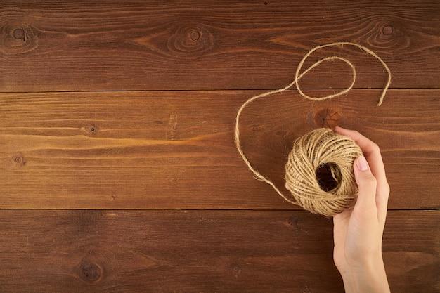 Vue de dessus d'une main féminine tricotant du fil de laine sur bois foncé