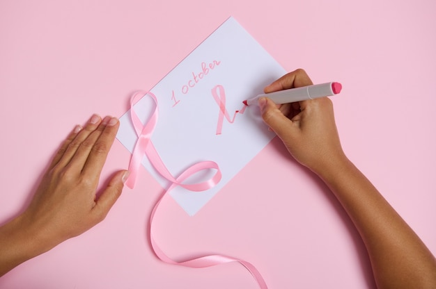 Vue de dessus d'une main de femme tenant un stylo-feutre écrit le 1er octobre et dessine sur le papier un symbole rose du mois de sensibilisation au cancer du sein, un ruban rose avec une extrémité sans fin, allongé sur un fond rose