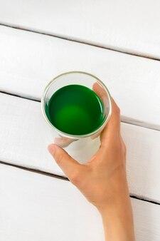 Vue de dessus de la main de femme tenant une tasse de boisson à la chlorophylle sur fond de bois blanc image verticale mise au point sélective