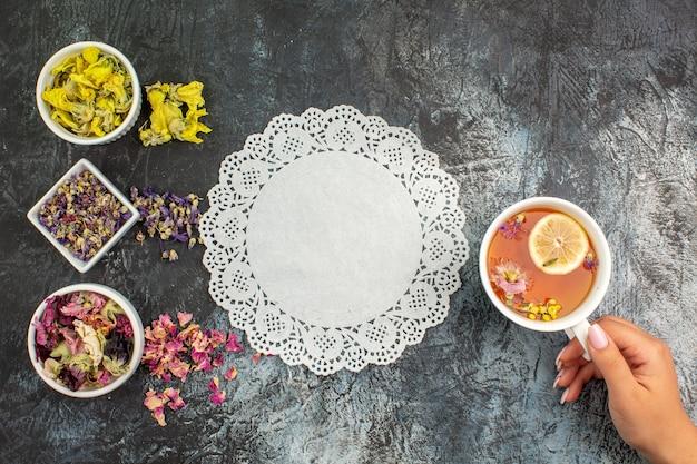 Vue de dessus de la main de femme tenant une tasse de tisane et bols de fleurs sèches avec de la dentelle sur fond gris
