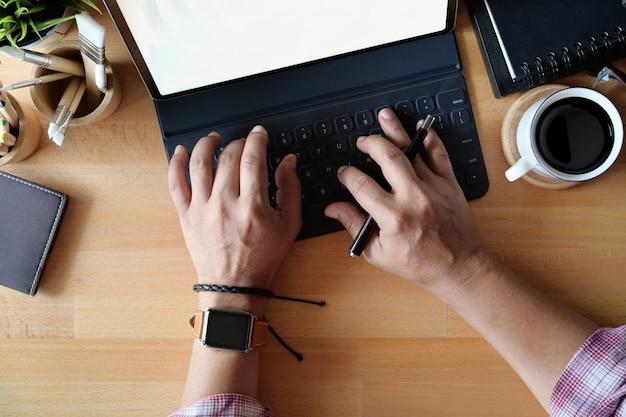 Vue de dessus de la main de freelance à l'aide de la tablette clavier sur l'espace de travail de bureau