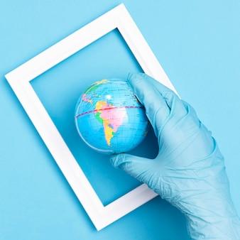 Vue de dessus de la main avec un gant chirurgical tenant le globe terrestre dans le cadre