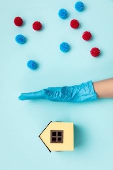 Vue de dessus main avec gant séparant les boules décoratives et la maison en papier