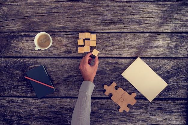 Vue de dessus de la main d'homme d'affaires organisant de petits blocs de bois sur une table rustique avec des notes et une tasse de café, effet rétro tonique.